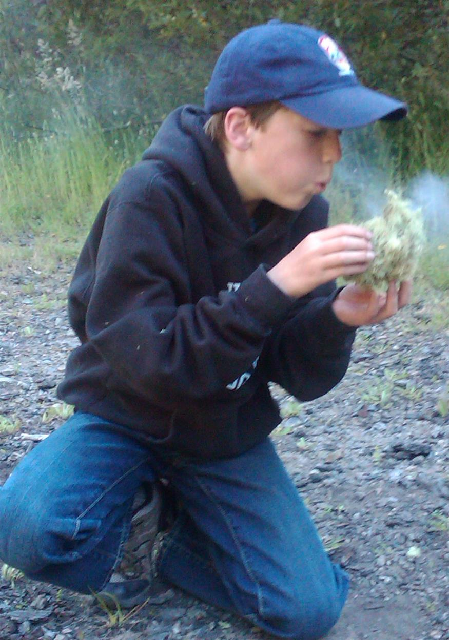 kid blowing coal into flames