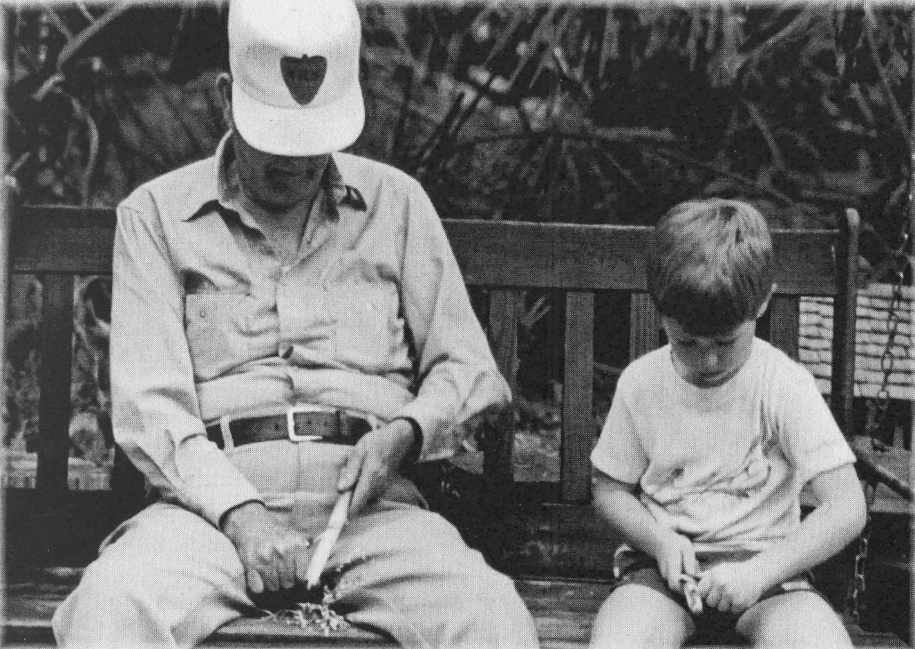 Grandfather and grandson whittling