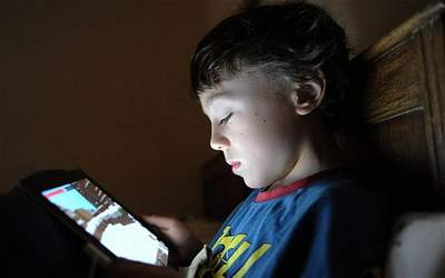 child playing with an iPand in bed